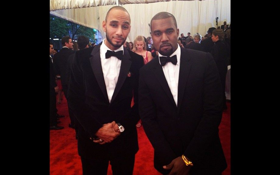 Swizz Beatz and Kanye West pose for the cameras, Swizz in a velvet suit and a bow tie with some sheen and Kanye in a classic black tux fastened with a satin black bow tie