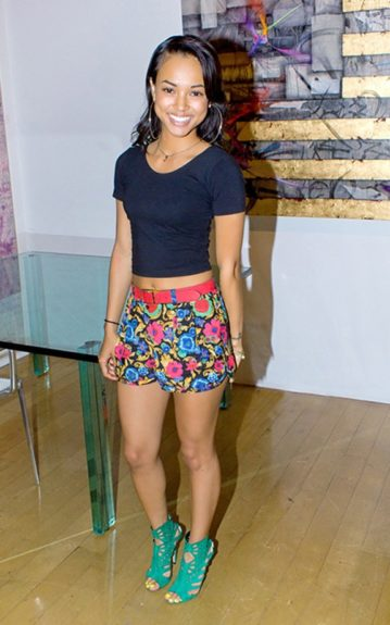 """Karrueche looks summery in a black cropped top, floral shorts and her emerald green Jimmy Choo 'Imogen"""" caged sandals, as she attends Chris Brown's art exhibit."""
