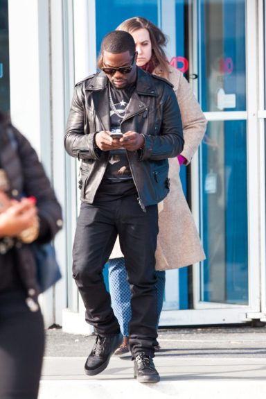 Too cool to pose for the paps, Kevin keeps busy on his cell as he does a press tour for film <em>Ride Along</em>, looking effortless in this all black ensemble offset by his leather bomber.