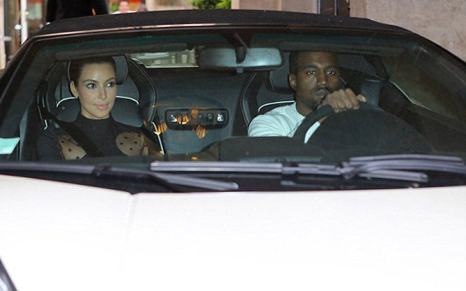 Kanye takes a break from black, in his white polo shirt (must be trying to match the Lambo). Kim looks hot in her Stella McCartney Lucia Sheer polka dot side dress.
