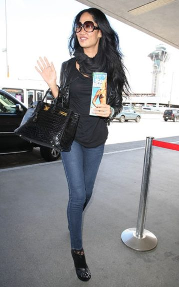 The fabulous Kimora Lee Simmons jets off to the airport casually in all black accessories. The studs on her booties add a rockstar-chic element