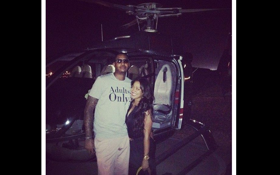 Lala and Carmelo take a helicopter ride in style. He wears a graphic tee, sunshades, and khaki pants. She wears a black low cut top, and black and white printed skirt