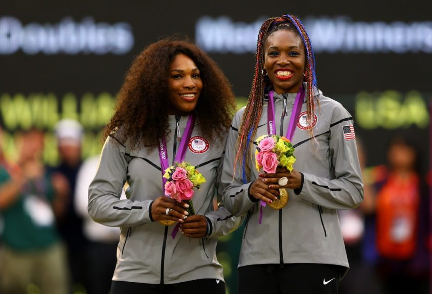 Serena rocks a natural inspired style, and Venus sports orange and blue two-stranded twists at the 2012 Olympics.