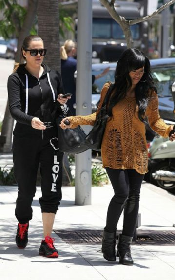 Khadijah Haqq strolls in style wearing a brown Mia Holes pullover by Torn by Ronny Kobo, jeans, and boots alongside her bestie Khloe Kardashian who's in black sweats