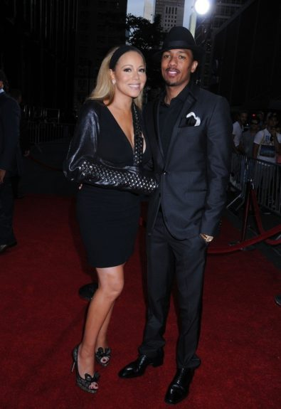 Mariah Carey posed it up with her hubby Nick Cannon rocking a velvet little black dress with a studded leather sleeve (that doubled as a cover-up for her cast), and Valentino Lace bow pumps. <em>Photo</em>: Getty