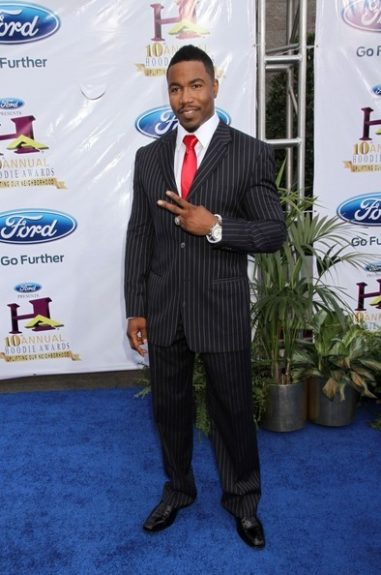 Michael Jai White wears a pinstriped black and white suit, crisp white button down, and a red tie. Photo Credit: Getty Images