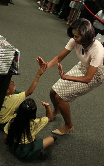 Michelle slaps high five, to 2 little ladies at her DC book signing, wearing a light pink Brooks Brothers silk cotton short sleeve keyhole sweater, and pewter and nude pop art polka dot J.Crew No.2 pencil skirt.
