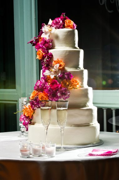 Simple and Elegant: The wedding cake was adorned with beautiful fuchsia and orange flowers