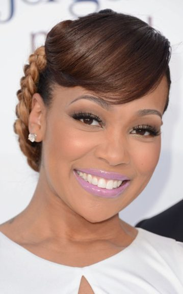 Monica wore a braided bun, bangs, and a pale pink lipstick with a classic pair of diamond stud earrings