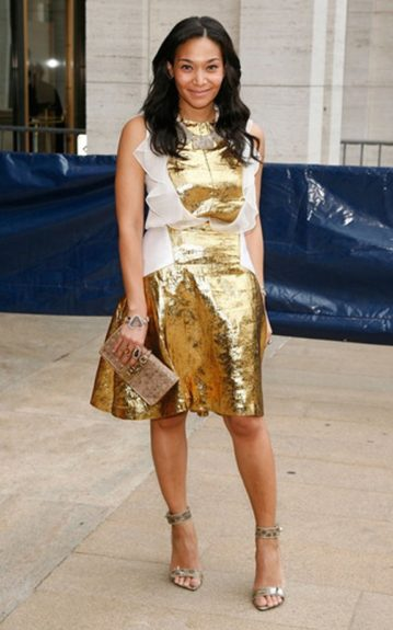 Jewelry designer, Monique Pean in a short, metallic gold dress with a sheer, white ruffle vest.