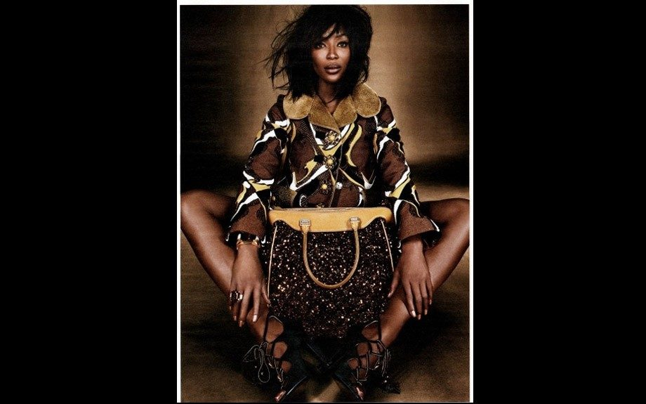 Naomi Campbell in recent photo shoot wore a brown and tan printed Louis Vuitton coat, strappy black Yves Saint Laurent pumps, and a large brown sparkle purse.