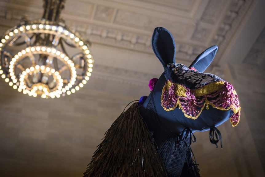 Profile of Nick Cave's horse soundsuit against the backdrop of Grand Central;Photo Credit by Travis Magee, Courtesy Creative Time and MTA Arts for Transit