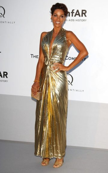 Nicole Murphy in a Marilyn Monroe-esque pleated gold metallic gown with gold accessories to match
