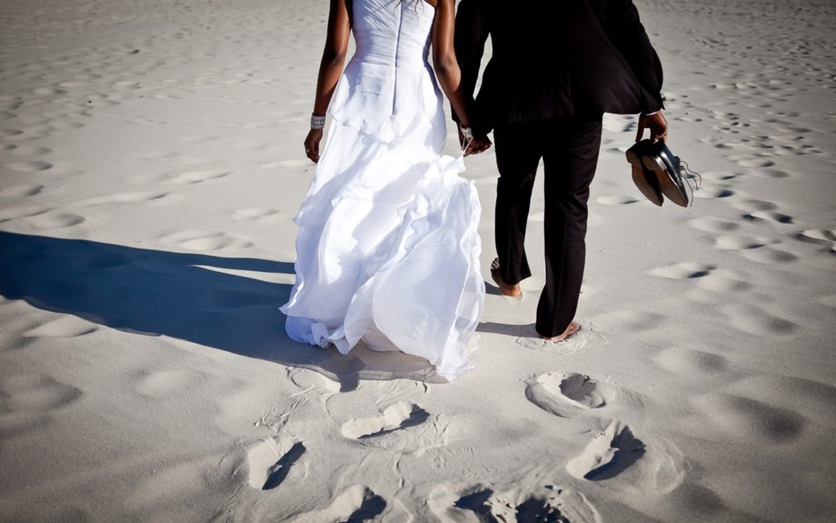 The couple Onyinye and Chima Gaiusand walk along the Cape Town sands leaving their wedded footsteps behind