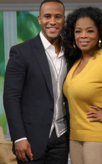 DeVon Franklin looks steamy in his black suit jacket, dark slacks, striped grey cardigan sweater, and off white button down. Oprah looks casual and cute in her mustard yellow sweater, khaki slacks, and gold hoop earrings