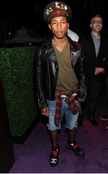 Pharrell aces the look in a red and black plaid top, a biker jacket and cool, customized combat boots