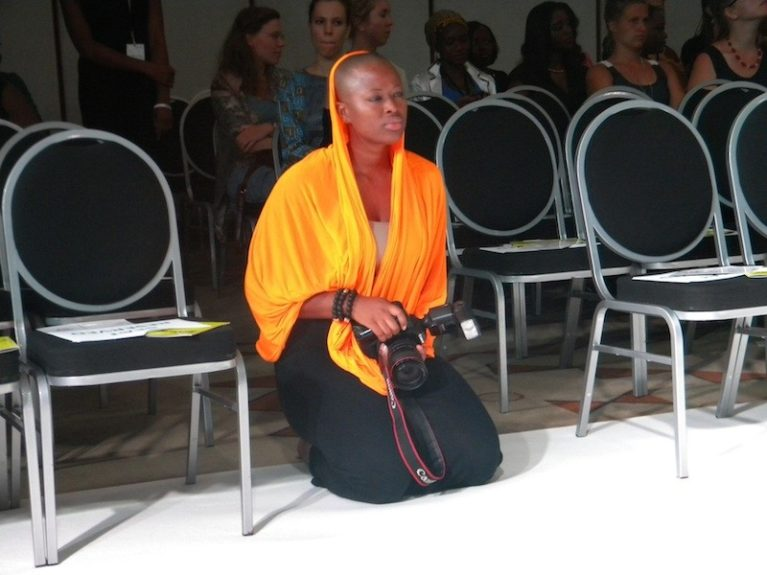 A photographer shoots the collection in a striking orange wrap