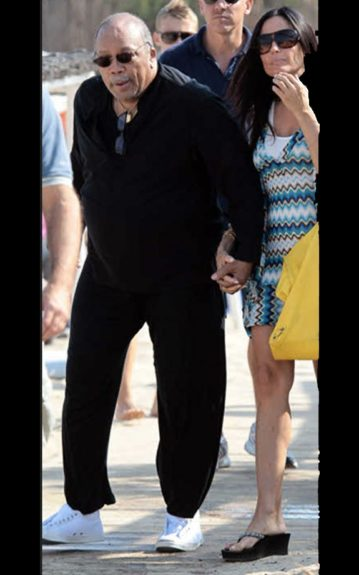 Quincy wears a black jogging suit, and white sneakers as his companion wears a striped knitted sundress, and black sandals. Photo Credit: INF
