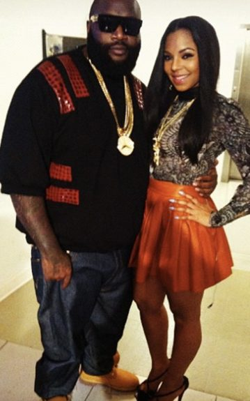 Rick Ross wears a black and red top, denim jeans, and Timberland boots. Ashanti wears a Alexander McQueen floral printed blouse, an Alice +Olive leather skirt, and Louboutin pumps. Photo Credit: Ashanti's Instagram