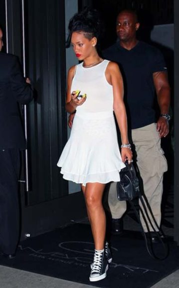 Rihanna looks gorgeous as she steps out in Soho, wearing a white A.L.C. Lena Flare dress, red lip, and black Converse sneakers. We're loving the pony as well!