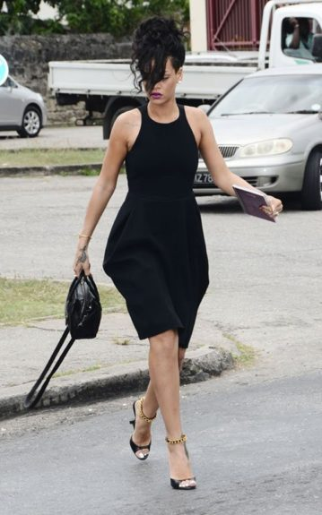 Rihanna tries to remain composed in her little black dress, and black Tom Ford pumps