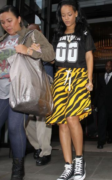 Rih is headed to the studio, looking casual in her Joyrich The NY athletic mesh top, yellow and black TRUKFIT printed shorts, and black Converses
