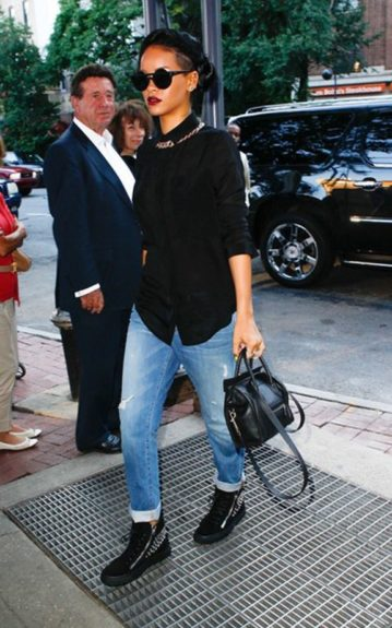 Rihanna took a stroll to Bang Bang tattoos for a new falcon tat. The rebel starlet is a showstopper in a T by Alexander Wang sheer black blouse, high top studded Giuseppe Zanotti sneakers, boyfriend jeans, and a mini Celine bag