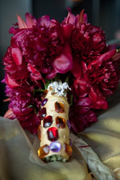 A charming bejeweled vase held the fuchsiaflower bouquet.