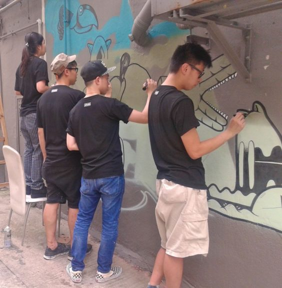 Street artists working on a mural in Sheung Wang.