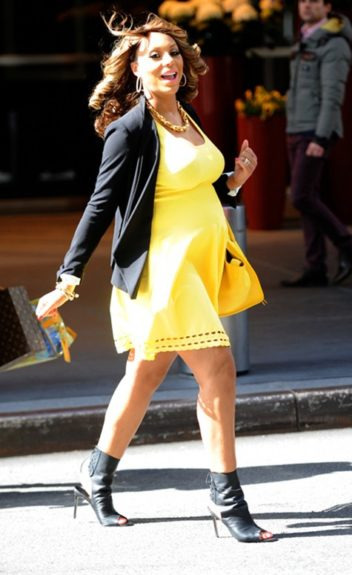 Always on the go, the previous mommy-to-be swings her Louis Vuitton as she headed out in a yellow Alexander McQueen dress with cutouts, a black BCBG blazer, and black Manolo Blahnik ankle boots. Her curly ringlets gave the outfit a romantic feel.
