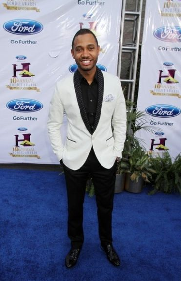 Terrance J wears a white blazer, black button down, black slacks, and black loafers on the blue carpet. Photo Credit: Getty Images