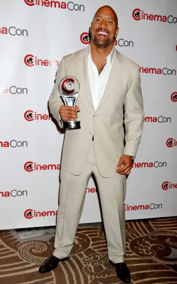 Dwayne Johnson smiles proudly with his award for Action Star of the Decade in-hand in a khaki suit and crisp white shirt buttoned down just enough to get a peek of some chest ink