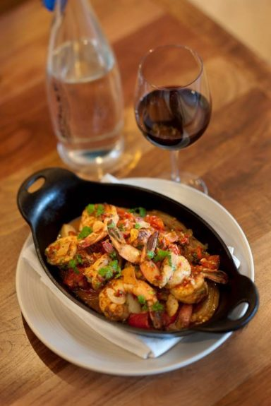 A flaming shrimp dish sets a glass of red off lovely