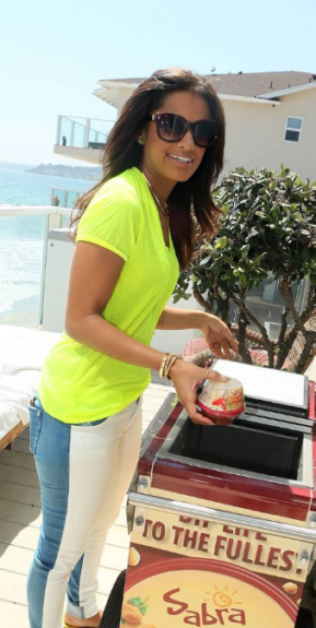 Rocsi Diaz noshing on delights provided by Sabra at the Kia Motors Beach House sponsored by Voli Light Vodkas and Owl's Brew.