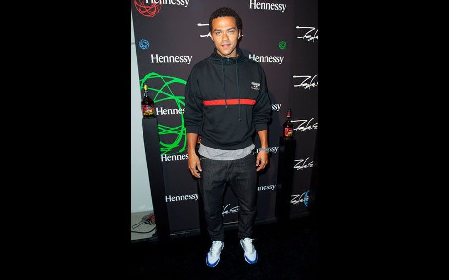 Jesse Williams wears a black hoodie with red accent, jeans, and Jordan sneakers, keeping his look very casual. Photo Credit: Getty