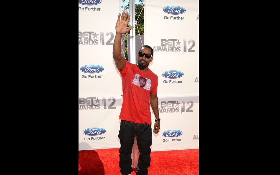 Jamie Foxx shows support for Trayvon Martin, wearing a shirt with his image on it, black jeans, and white sneakers.