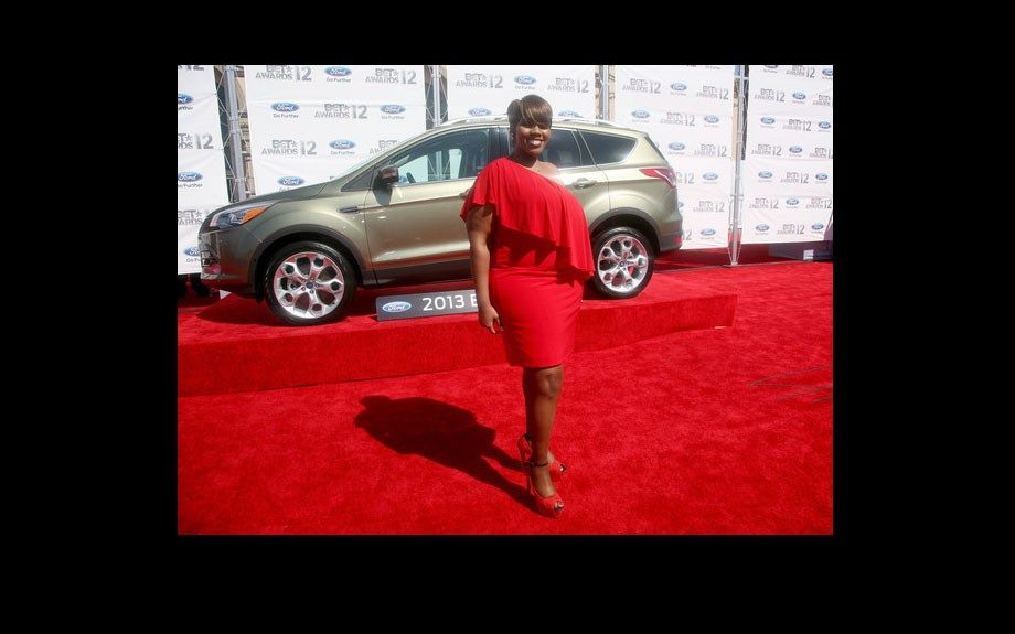 Kelly Price goes red in a one shoulder dress, with a ruffle, and red heels.
