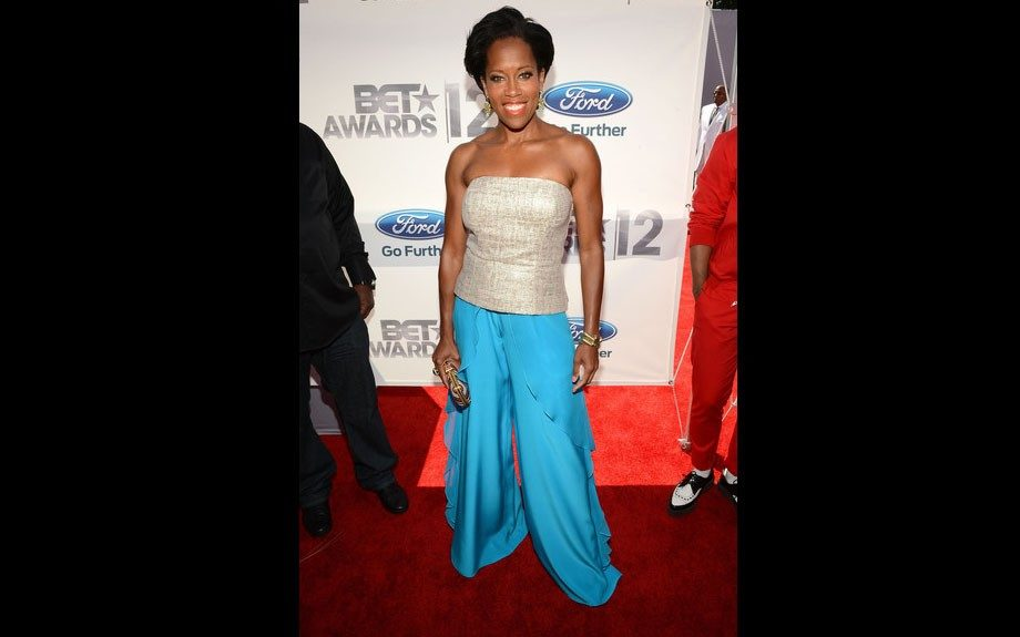 Regina King wears flowy blue pants with ruffles, and a pale gold tube top on the red carpet.