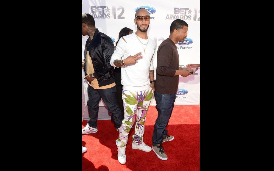 Swizz Beats goes tropical with his jungle pants, and white long sleeve shirt.