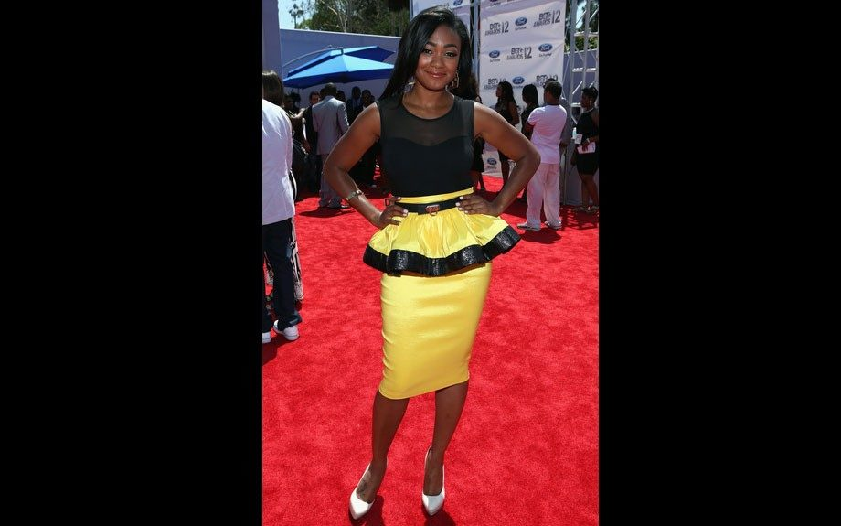 Tatyana Ali wears a black top and yellow pencil skirt with a ruffle, and black trim.