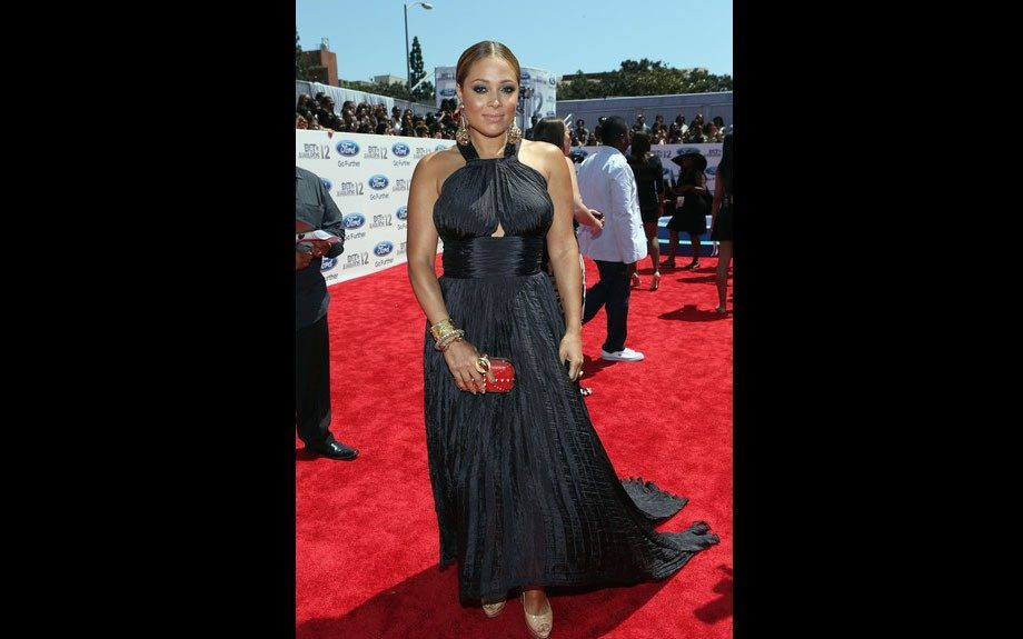 Tamia's back on the scene, and she looks stunning. She wears a black Oscar de la Renta gown, red Alexander McQueen studded clutch, and nude pumps.