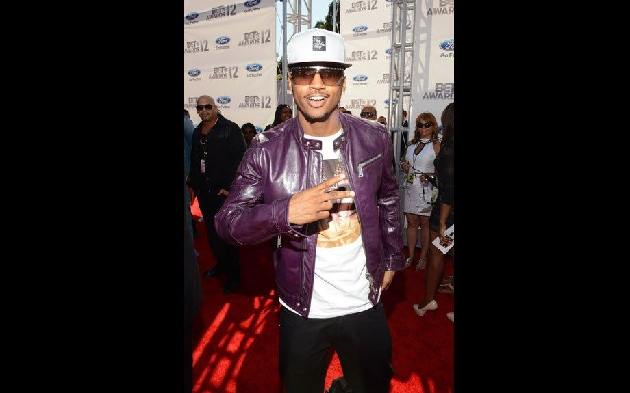 Trey Songz never lacks in the sex appeal department, wearing a purple leather jacket, printed shirt, white snapback, and black jeans.