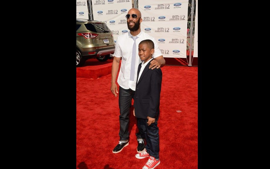 Common wears a white button down, blue tie, dark jeans, and black shiny sneakers on the red carpet.