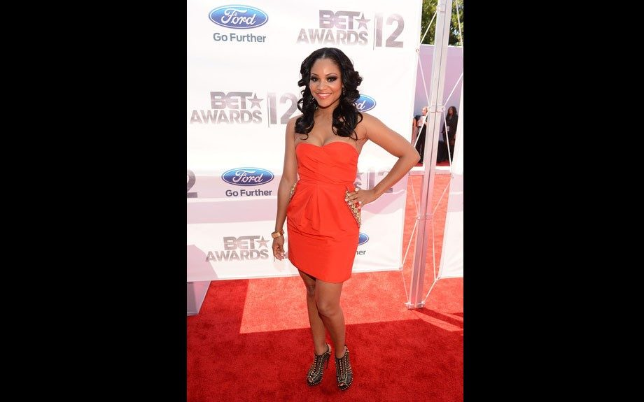Erica Hubbard is working her strapless tangerine dress, and brown embellished sandal heels.