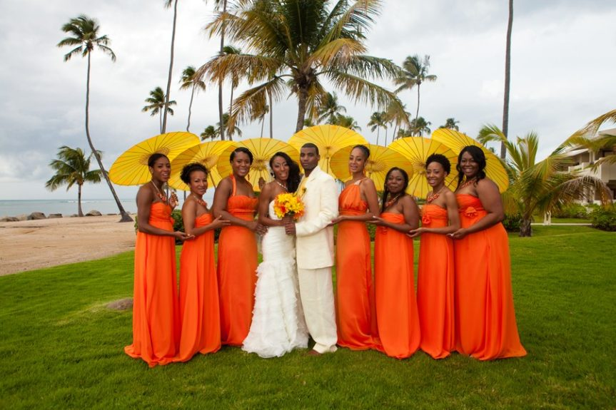 Bride and groom Lachelle Robinson and Larry Sesson join the bridal party. The ladies wore orange halter maxi dresses with yellow umbrellas as an accessory
