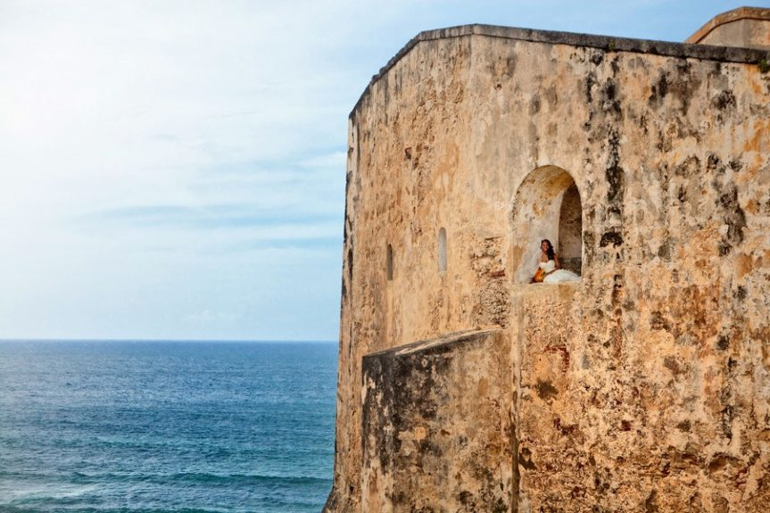 The bride Lachelle Robinson in her princess moment in a distant open window overlooking the San Juan ocean