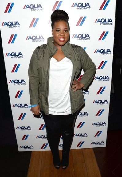 Amber Riley shows off her super cute braids as she rocks a military jacket and red lip. <em>Photo</em>: INF