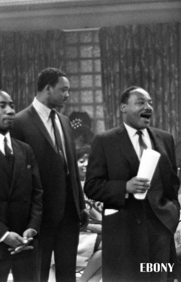 Dr. Martin Luther King Jr. speaking as Rev. Jesse Jackson listens on. (Isaac Sutton/ EBONY Collection)