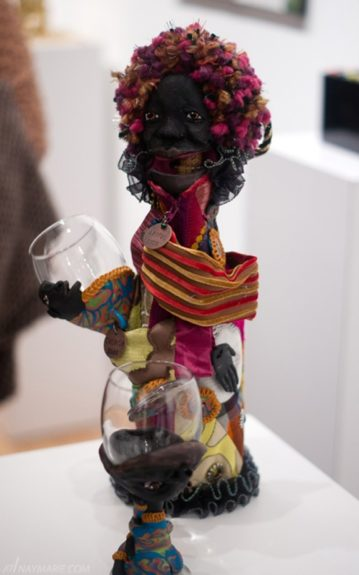 Laura Gadson, Mouth-to-Mouth Libation, 2012. Wine bottle and wineglass embellished with polymer clay, paint, quilt and embroidered fabric, 3 pieces (triptych/ 1 bottle and 2 glasses), 15 x 10 in.