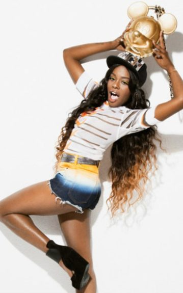 Azealia Banks goes playful and cute in recent photo shoot. She shows her inner child in tie-dye denim shorts, a striped tee, fitted cap, long ombre hair, and a Mickey Mouse trophy.